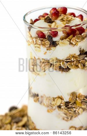 Glass Of Muesli With Fruits And Yogurt Isolated On White