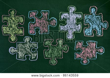 some puzzle pieces drawn with chalk of different colors on a green chalkboard, as the symbol for the autism awareness