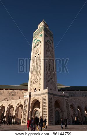 CASABLANCA, MOROCCO - MAR 8 2015 : Visitors stroll beneath the impressive Hassan II mosque minaret .