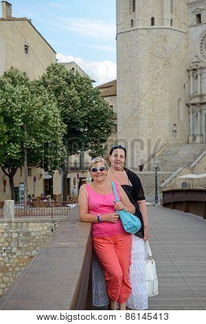 Two Women On Sant Feliu Bridge In Girona, Spain.