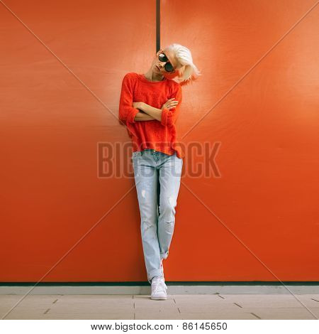 Stylish Blonde Stand Near Red Wall On City Street. Urban Casual Style