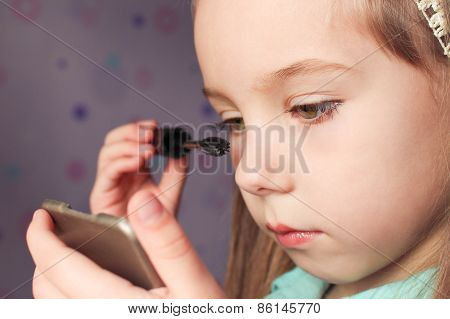 Little girl paints the eyes mascara