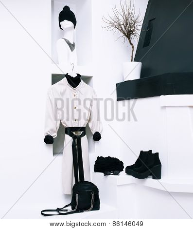Fashionable Women's Coats And Accessories In A White Interior. Black And White Combination In Clothi