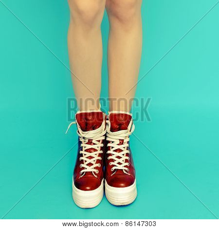 Girl Legs In Red Vintage Sneakers On Blue Background