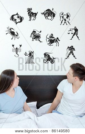 Man And Surprised Woman In Bedroom Surrounded Looking Up At Horoscope
