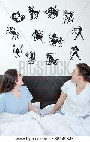Man And Surprised Woman In Bedroom Surrounded Looking Up At Horoscope Zodiac
