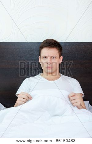 Surprised And Shocked Good Looking Young Man In Bed Looking Down