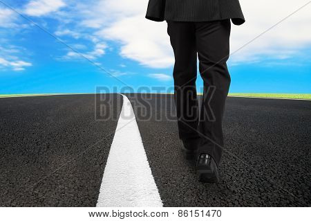 Businessman Walking On Asphalt Road With Sky Clouds