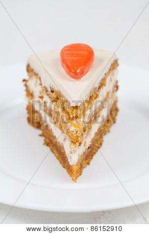 Delicious slice of carrot sponge cake with cream and walnut