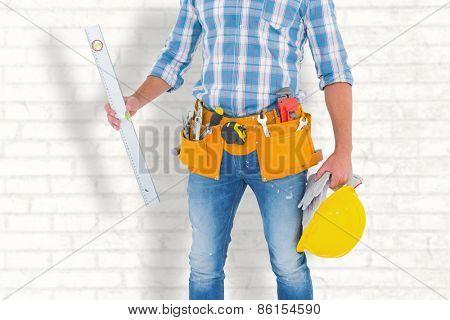 Manual worker holding spirit level against white wall
