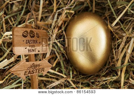 Easter egg hunt sign against golden egg in the straw
