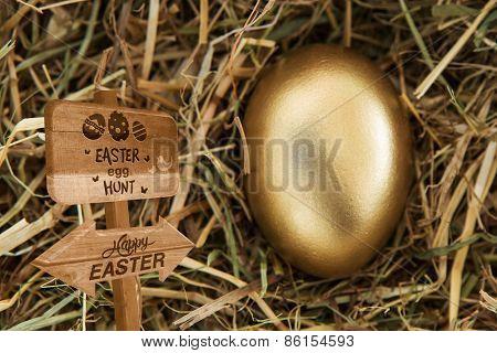 Easter egg hunt sign against golden egg in the straw
