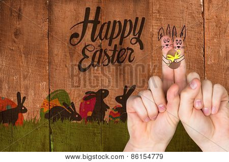 Fingers as easter bunny against wooden planks