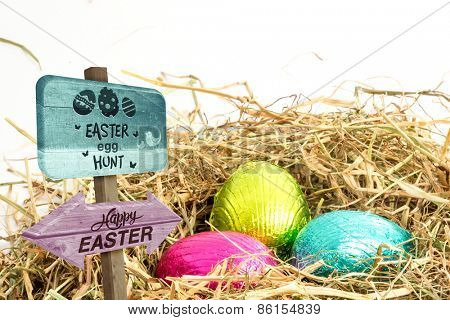 Easter egg hunt sign against three easter eggs nestled in straw nest