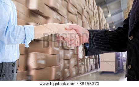 Close up of a business people closing a deal against forklift machine in warehouse