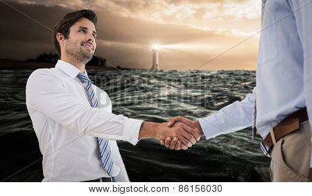 Young businessmen shaking hands in office against stormy sea with lighthouse