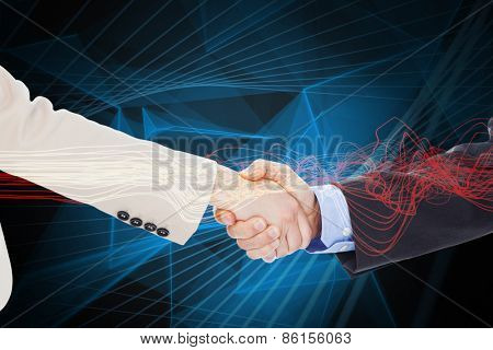 Smiling business people shaking hands while looking at the camera against blue design