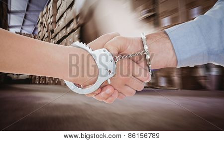 Handcuffed business people shaking hands against worker with fork pallet truck stacker in warehouse