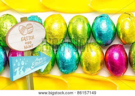 Easter egg hunt sign against colourful foil wrapped easter eggs with tulip petals