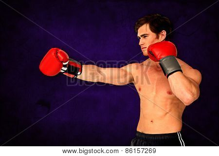 Muscly man wearing red boxing gloves and punching against dark background