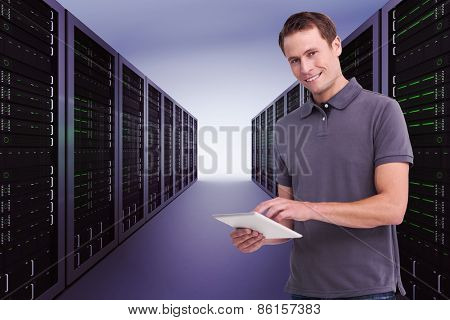 Smiling young man with tablet computer against server hallway