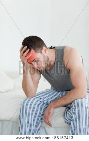 Portrait of an exhausted man sitting on his bed while looking away from the camera