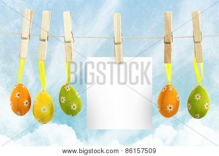 hanging easter eggs against painted blue sky