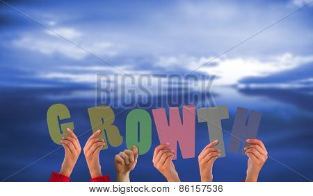 Hands showing growth against blue sky with blue clouds