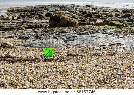 Solitary Green Childs Bucket Has Been Left Behind On A Pebble Beach