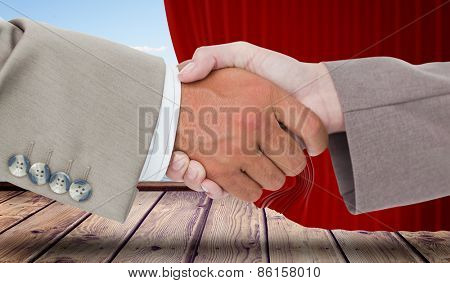 Side view of business peoples hands shaking against curtain pulled back to show harbour
