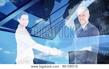 Smiling business people shaking hands while looking at the camera against skyscraper