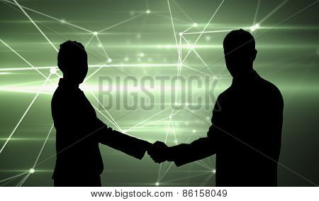 Smiling business people shaking hands while looking at the camera against glowing geometric design