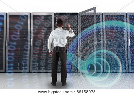 Businessman standing back to the camera pointing against binary spiral with blue glow