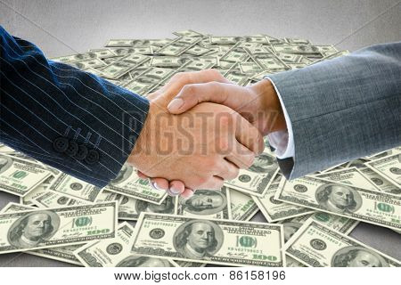 Business people shaking hands against pile of dollars