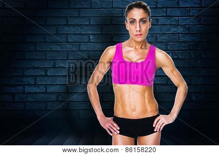 Female bodybuilder posing with hands on hips looking at camera against black background