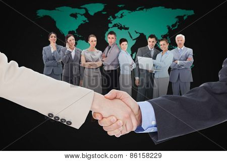 Smiling business people shaking hands while looking at the camera against black world map