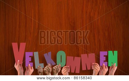 Hands holding up velkommen against wooden oak table