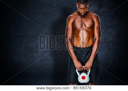 Shirtless fit young man lifting kettle bell against black background