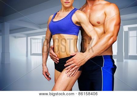 Bodybuilding couple against white room with windows