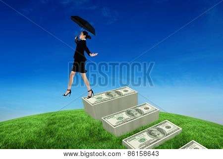 Young businesswoman holding umbrella against green hill under blue sky