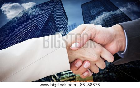Close up on partners shaking hands against low angle view of skyscrapers