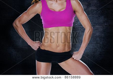 Female bodybuilder posing in pink sports bra and shorts mid section against black background