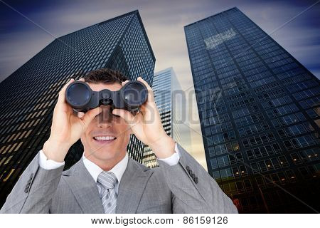 Businessman holding binoculars against low angle view of skyscrapers