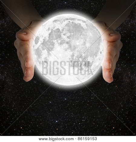 man holding the moon in the hands against the background of the galaxy.