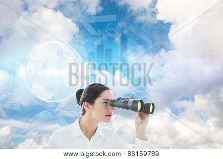 Business woman looking through binoculars against global business graphic in blue
