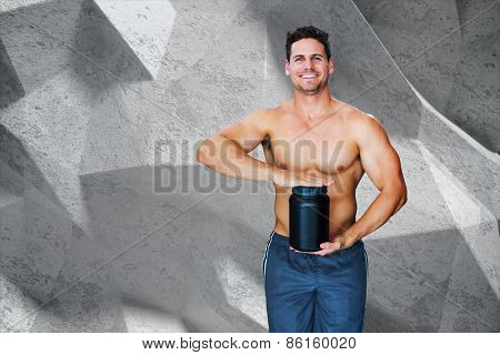 Bodybuilder with protein powder against grey angular background