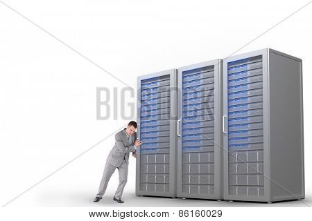 Portrait of a handsome businessman pushing a wall against three digital grey server towers