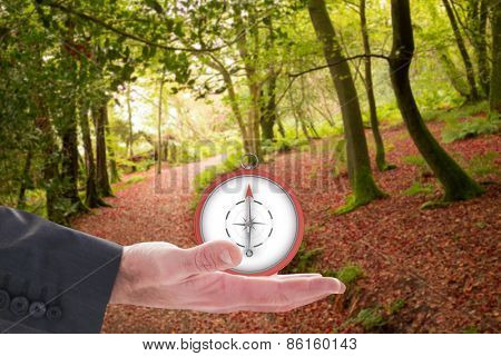 Businessman holding hand out in presentation against peaceful autumn scene in forest