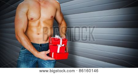 Attractive bodybuilder with gifts against grey shutters