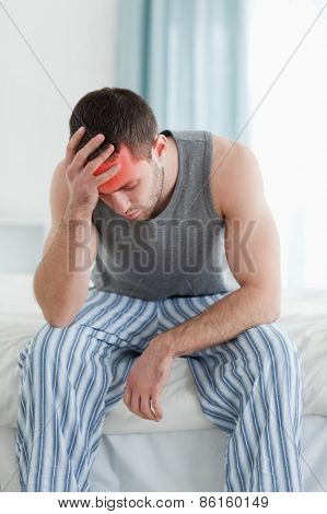 Portrait of a sad man sitting on his bed
